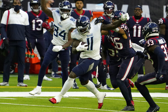 Tennessee Titans wide receiver A.J. Brown (11) is tackled by Houston Texans cornerback Vernon Hargreaves III (26) after catching a pass during the second half of an NFL football game Sunday, Jan. 3, 2021, in Houston. (AP Photo/Sam Craft)