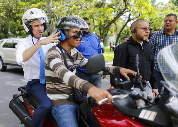 Juan Guaido, Venezuelan opposition leader, and self-proclaimed interim president of Venezuela, adjusts the helmet on a motorcycle driver as he is  driven from the Central University of Venezuela after a meeting with students, in Caracas, Venezuela, Thursday, Nov. 14, 2019. (AP Photo/Ariana Cubillos)