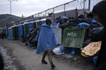 A migrant covered with a blanket passes in front of dumped garbage outside the Moria refugee camp on the northeastern Aegean island of Lesbos, Greece, on Tuesday, Jan. 21, 2020. Some businesses and public services on the eastern Aegean island are holding a 24-hour strike on Wednesday to protest the migration situation, with thousands of migrants and refugees are stranded in overcrowded camps in increasingly precarious conditions.(AP Photo/Aggelos Barai)