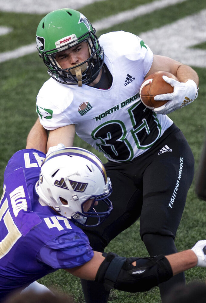 North Dakota running back Dalton Gee (35) gets tackled by James Madison defensive lineman Mike Wilcox (47) during the first half of a quarterfinal game in the NCAA FCS football playoffs in Harrisonburg, Va., Sunday, May 2, 2021. (Daniel Lin/Daily News-Record via AP)
