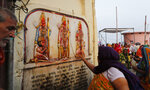 A Hindu pilgrim touches in obeisance an image of Hindu god Rama his wife Sita and his brother Lakshman in Ayodhya, India , Saturday, Nov. 9, 2019. India's security forces were on high alert ahead of the Supreme Court's verdict Saturday in a decades-old land title dispute between Muslims and Hindus over plans to build a Hindu temple on a site where Hindu hard-liners demolished a 16th century mosque in 1992, sparking deadly religious riots. (AP Photo/Rajesh Kumar Singh)