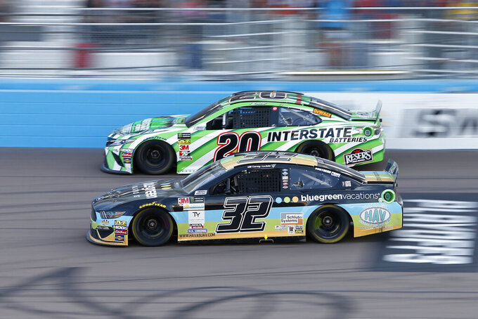 Corey LaJoie (32) and Erik Jones (20) race side-by-side during the NASCAR Cup Series auto race at ISM Raceway, Sunday, Nov. 10, 2019, in Avondale, Ariz. (AP Photo/Ralph Freso)