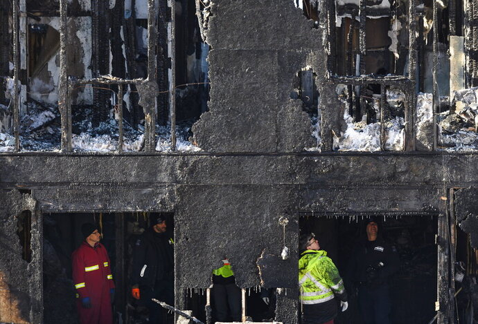 Police and firefighters investigate following a house fire in the Spryfield community in Halifax, Nova Scotia, Tuesday, Feb. 19, 2019. Seven children, all members of a Syrian family who arrived in Canada about two years ago, died in the early morning fire Tuesday that witnesses said quickly engulfed a home in a Halifax suburb. (Darren Calabrese/The Canadian Press via AP)