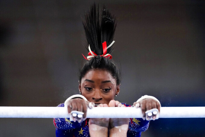 Simone Biles, of the United States, performs on the uneven bars during the women's artistic gymnastic qualifications at the 2020 Summer Olympics, Sunday, July 25, 2021, in Tokyo. (AP Photo/Ashley Landis)