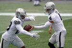 Las Vegas Raiders quarterback Derek Carr (4) hands off to running back Josh Jacobs (28) in the first half of an NFL football game against the New England Patriots, Sunday, Sept. 27, 2020, in Foxborough, Mass. (AP Photo/Charles Krupa)