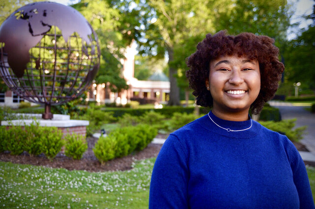 """In a photo provided by Belhaven University, aspiring author Imani Skipwith poses for a photo on the Belhaven campus in Jackson, Miss., April 20, 2020. Skipwith is the first recipient of the Angie Thomas Scholarship, which Belhaven created to honor the author of bestselling young-adult novels. Thomas is a 2011 Belhaven graduate who wrote """"The Hate U Give"""" and """"On the Come Up,"""" and she is working on her third novel. Skipwith is graduating from the Mississippi School of the Arts, and she submitted samples of her writing to apply for the scholarship at Belhaven. (David Sprayberry/Belhaven University via AP)"""