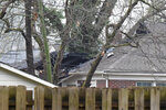 Damage is visible following a small plane crash during dense fog in a residential neighborhood on Wednesday, Jan. 13, 2021, in Columbia, S.C. Officials say the woman home at the time safely escaped after the crash caused a fire that damaged her roof and house. (AP Photo/Meg Kinnard)