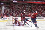 Washington Capitals right wing Tom Wilson (43) celebrates his goal with left wing Alex Ovechkin (8), of Russia, and center Evgeny Kuznetsov (92), of Russia, against Carolina Hurricanes goaltender Petr Mrazek (34), of the Czech Republic, defenseman Jaccob Slavin (74), defenseman Brett Pesce (22) during the third period of Game 5 of an NHL hockey first-round playoff series, Saturday, April 20, 2019, in Washington. The Capitals won 6-0. (AP Photo/Nick Wass)