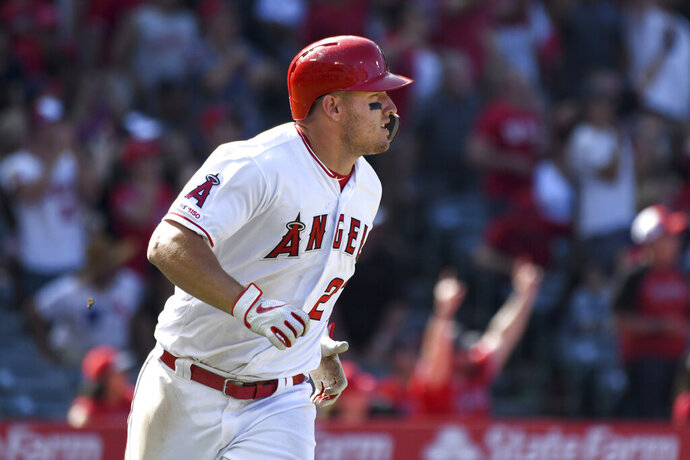 Los Angeles Angels' Mike Trout watches his two-run home run during the sixth inning against the Texas Rangers in a baseball game Sunday, April 7, 2019, in Anaheim, Calif. (AP Photo/Michael Owen Baker)
