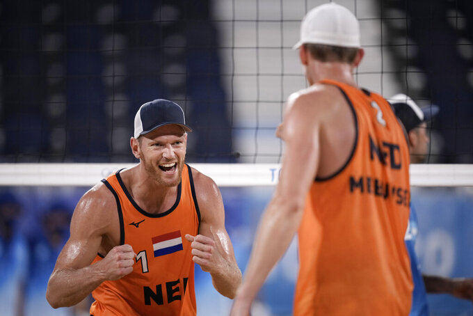Alexander Brouwer, left, of the Netherlands, celebrates with teammate Robert Meeuwsen after winning a men's beach volleyball match against Argentina at the 2020 Summer Olympics, Tuesday, July 27, 2021, in Tokyo, Japan. (AP Photo/Felipe Dana)