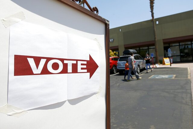 Voters walk to a polling station to cast votes for GOP and Democratic primary candidates Tuesday, Aug. 4, 2020, in Chandler, Ariz. (AP Photo/Ross D. Franklin)