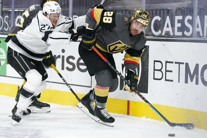 Vegas Golden Knights left wing William Carrier (28) passes around Los Angeles Kings left wing Austin Wagner (27) during the second period of an NHL hockey game Monday, March 29, 2021, in Las Vegas. (AP Photo/John Locher)