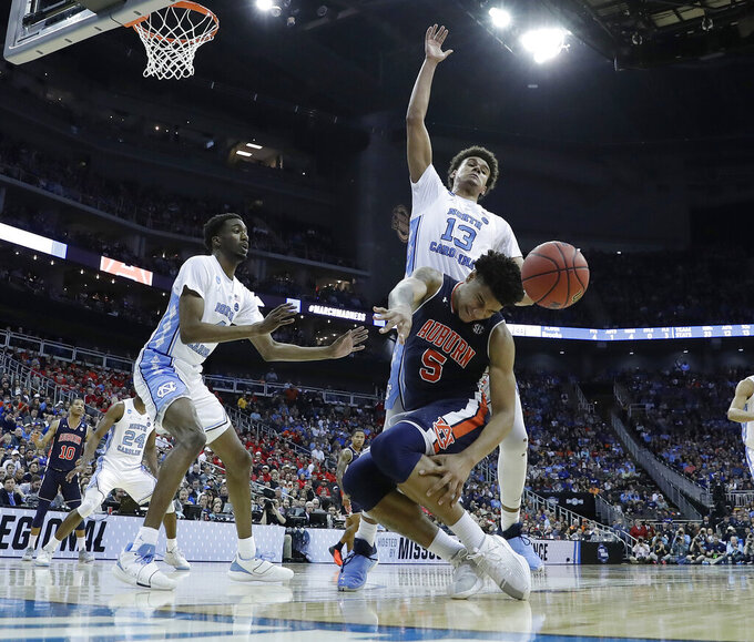 Auburn's Chuma Okeke (5) loses control of the ball as he collides with North Carolina's Cameron Johnson (13) and North Carolina's Brandon Robinson, left, watches during the second half of a men's NCAA tournament college basketball Midwest Regional semifinal game Friday, March 29, 2019, in Kansas City, Mo. Okeke was injured on the play. (AP Photo/Charlie Riedel)