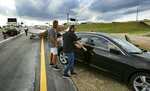 The driver, right, of a black Acura that was struck by a small plane, background, making an emergency landing on the eastbound ramp of Maitland Blvd. to Interstate 4, retrieves personal belongings from his car on Thursday, May 16, 2019, in Maitland, Fla. (Joe Burbank/Orlando Sentinel via AP)