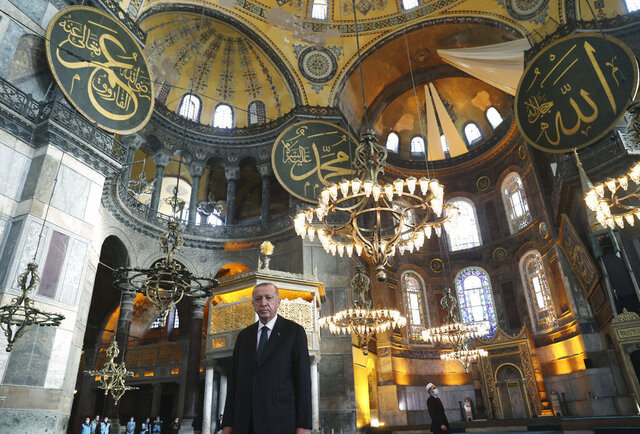 Turkey's President Recep Tayyip Erdogan poses for photographs after Friday prayers inside Hagia Sophia Mosque, in Istanbul, Friday, Dec. 4, 2020. Erdogan has renewed his vitriolic attacks on French President Emmanuel Macron, saying he hopes France will get rid of him soon. Erdogan called Macron