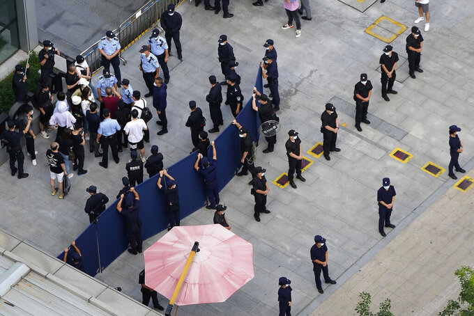 Investors are surrounded by police and security personnel as they try to enter the headquarters of the real estate developer Evergrande Group, Thursday, Sept. 23, 2021, in Shenzhen, southern China. Fears that the developer's possible default on multibillion-dollar debts might send shockwaves through global financial markets appeared to ease Thursday as creditors waited to see how much they might recover. (AP Photo/Ng Han Guan)