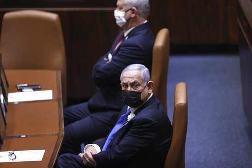 Israeli Prime Minister Benjamin Netanyahu, front, attends the swearing-in ceremony for Israel's 24th government, at the Knesset, or parliament, in Jerusalem, Tuesday, April 6, 2021. The ceremony took place shortly after the country's president asked Netanyahu to form a new majority coalition, a difficult task given the deep divisions in the fragmented parliament. (Alex Kolomoisky/Pool via AP)