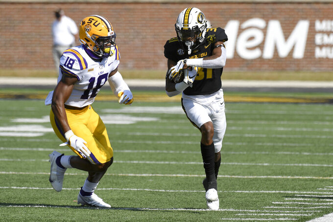 Missouri wide receiver D'ionte Smith, right, runs with the ball before being knocked out of bounds by LSU linebacker Damone Clark (18) during the first half of an NCAA college football game Saturday, Oct. 10, 2020, in Columbia, Mo. (AP Photo/L.G. Patterson)