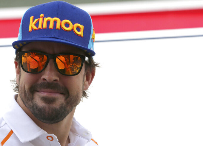 FILE - In this Sunday, Nov. 25, 2018 file photo, Mclaren driver Fernando Alonso of Spain arrives ahead of the Emirates Formula One Grand Prix at the Yas Marina racetrack in Abu Dhabi, United Arab Emirates. The season starts Sunday March 28, 2021 with the Bahrain Grand Prix and ends in December 2021 at Abu Dhabi. Two-time world champion Fernando Alonso is back after missing the past two seasons. (AP Photo/Kamran Jebreili, File)
