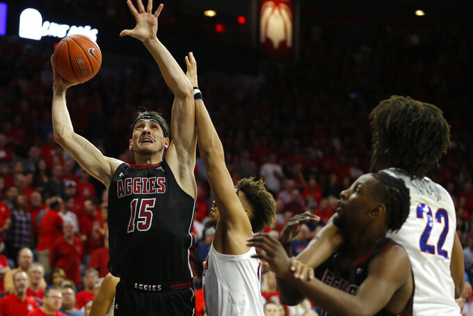 New Mexico State forward Ivan Aurrecoechea (15) shoots over Arizona center Chase Jeter (4) in the first half during an NCAA college basketball game, Sunday, Nov. 17, 2019, in Tucson, Ariz. (AP Photo/Rick Scuteri)