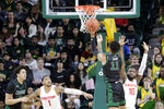 George Mason's Jordan Miller (11) shoots the ball as Dayton's Obi Toppin (1) and Jalen Crutcher (10) defend during the first half of an NCAA college basketball game, Tuesday, Feb. 25, 2020, in Fairfax, Va. (AP Photo/Luis M. Alvarez)