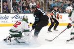 Minnesota Wild goaltender Alex Stalock (32) deflects a shot by San Jose Sharks' Evander Kane (9) during the first period of an NHL hockey game Thursday, Nov. 7, 2019, in San Jose, Calif. (AP Photo/John Hefti)