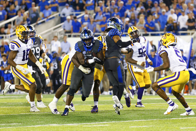 Kentucky running back Kavosiey Smoke (0) fights through the LSU defense during the second half of an NCAA college football game in Lexington, Ky., Saturday, Oct. 9, 2021. (AP Photo/Michael Clubb)