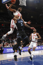 St. John's LJ Figueroa (30) blocks a shot by Villanova's Justin Moore (5) during the first half of an NCAA college basketball game Tuesday, Jan. 28, 2020, in New York. (AP Photo/Frank Franklin II)
