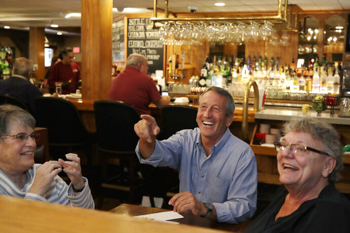 Republican presidential candidate, former South Carolina Gov. Mark Sanford chats withpatrons at the Puritan Backroom restaurant, as he campaigns, Thursday, Sept. 19, 2019, in Manchester, N.H. (AP Photo/Elise Amendola)