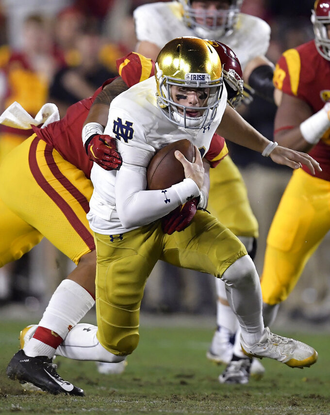 Notre Dame quarterback Ian Book is sacked by Southern California linebacker Palaie Gaoteote IV during the first half of an NCAA college football game Saturday, Nov. 24, 2018, in Los Angeles. (AP Photo/Mark J. Terrill)