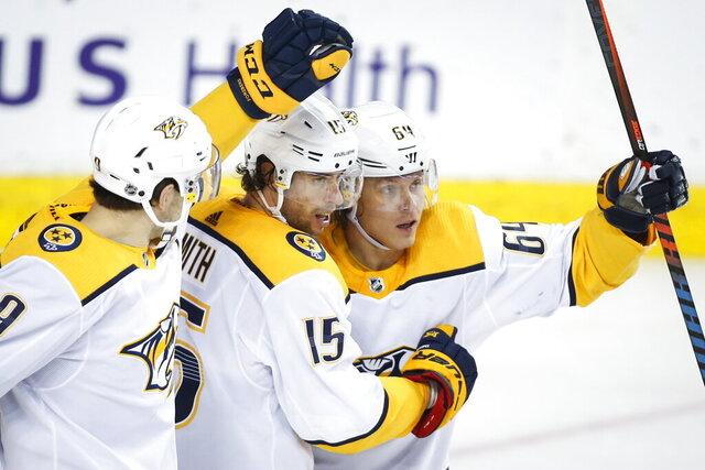 Nashville Predators' Mikael Granlund, right, celebrates his goal with teammates Craig Smith, center, and Filip Forsberg during second-period NHL hockey game action against the Calgary Flames in Ottawa, Ontario, Thursday, Feb. 6, 2020. (Fred Chartrand/The Canadian Press via AP)