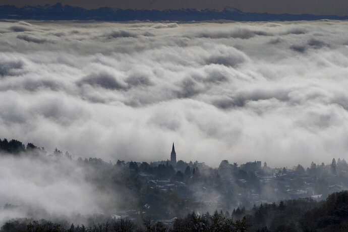 The village of Saint Cyr au Mont d'Or, around Lyon, central France, is seen through the clouds, Friday, Nov. 15, 2019. A dump of heavy snow in southern France has brought down power lines and trees, killing one person, and caused widespread traffic disruption. (AP Photo/Laurent Cipriani)