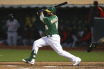 Oakland Athletics' Mitch Moreland hits an RBI single against the Detroit Tigers during the fourth inning of a baseball game in Oakland, Calif., Friday, April 16, 2021. (AP Photo/Jed Jacobsohn)