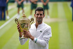 FILE - In this July 11, 2021, file photo, Serbia's Novak Djokovic holds the trophy after his win over Italy's Matteo Berrettini in the men's singles final match of the Wimbledon Tennis Championships in London. Djokovic is 26-0 in Grand Slam matches in 2021, moving him two victories away from being the first man to win all four major tennis championships in one season since Rod Laver in 1969.  (AP Photo/Alberto Pezzali, Pool)