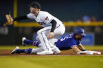 Texas Rangers' Nick Solak dives back safely on a pick-off attempt as Arizona Diamondbacks' Pavin Smith, left, makes the catch during the first inning of a baseball game, Tuesday, Sept. 7, 2021, in Phoenix. (AP Photo/Matt York)