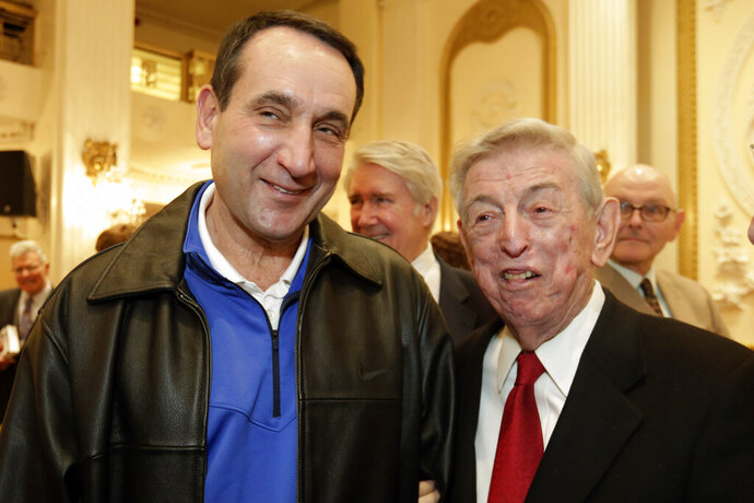 FILE - In this Nov. 20, 2015, file photo, Duke basketball coach Mike Krzyzewski, left, winner of the Lapchick Character Award, gets together with former St. John's basketball coach Lou Carnesecca at the organization's annual luncheon, in New York. Krzyzewski and Carnesecca are among those who teamed up with Madison Square Garden for a video posted on social media Wednesday night, May 13, 2020, saluting essential workers leading the fight against the coronavirus. (AP Photo/Richard Drew, File)