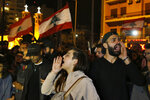 Protesters chant slogans and hold their national flags as they block a highway during an anti-government protest in Beirut, Lebanon, Wednesday, Dec. 4, 2019. Protesters have been holding demonstrations since Oct. 17 demanding an end to corruption and mismanagement by the political elite that has ruled the country for three decades. (AP Photo/Bilal Hussein)