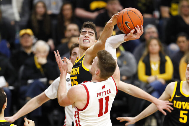 Iowa center Luka Garza blocks a shot by Wisconsin forward Micah Potter (11) during the first half of an NCAA college basketball game, Monday, Jan. 27, 2020, in Iowa City, Iowa. (AP Photo/Charlie Neibergall)