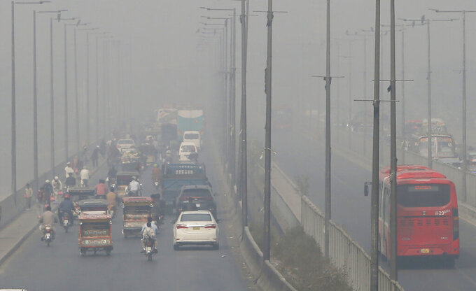 Vehicles drive on a highway as smog envelops the area of Lahore, Pakistan, Wednesday, Nov. 11, 2020. People in Pakistan's cultural capital of Lahore were at risk of respiratory diseases and eye-related problems Wednesday after the air quality deteriorated to hazardous levels due to a quilt of smog over the city, prompting doctors to urge people to stay at home. (AP Photo/K.M. Chaudary)