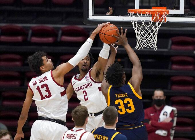Stanford forward Oscar da Silva (13) blocks California forward D.J. Thorpe (33) during the first half of an NCAA college basketball game in Stanford, Calif., Sunday, Feb. 7, 2021. (AP Photo/Tony Avelar)