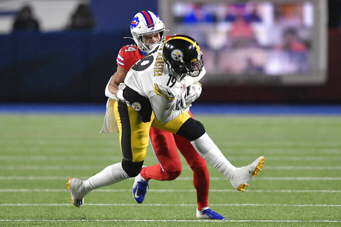 Pittsburgh Steelers wide receiver JuJu Smith-Schuster (19) comes down with a pass in front of Buffalo Bills cornerback Josh Norman (29) during the first half of an NFL football game in Orchard Park, N.Y., Sunday, Dec. 13, 2020. (AP Photo/Adrian Kraus)