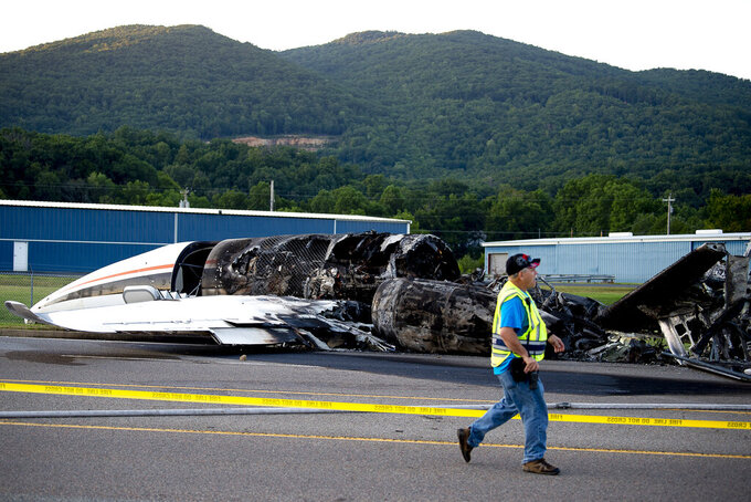 FILE - In this Aug. 15 2019, file photo, the burned remains of a plane that was carrying NASCAR television analyst and former driver Dale Earnhardt Jr., his wife Amy, 15-month-old daughter Isla, two pilots and the family dog lies near a runway at Elizabethton Municipal Airport in Elizabethton, Tenn. Earnhardt Jr. and a pilot struggled to open a crashed airplane's rear exit door as the aircraft began to burn and fill with smoke before the race car driver and his family managed to escape from the main door, according to new details about the 2019 accident released by the National Transportation and Safety Board.(Calvin Mattheis/Knoxville News Sentinel via AP, File)