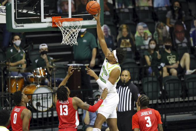South Florida's Michael Durr shoots past Houston defenders Marcus Sasser (0), J'Wan Roberts (13) and DeJon Jarreau (3) during the first half of an NCAA college basketball game Wednesday, Feb. 10, 2021, in Tampa, Fla. (AP Photo/Mike Carlson)