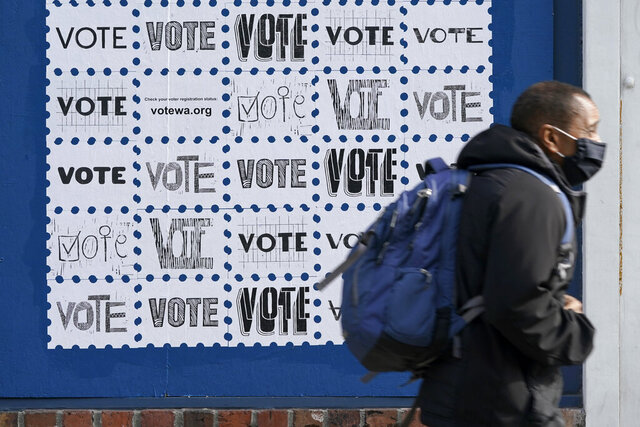 A pedestrian passes by a mural encouraging people to in Washington state to vote, Tuesday, Oct. 13, 2020, in downtown Seattle. A record number of voters in Washington have already returned their ballots as of Friday, Oct. 30, 2020, and other voters have until 8 p.m. Tuesday, Nov. 3, 2020 to drop off or mail their ballots or vote in person. (AP Photo/Ted S. Warren)