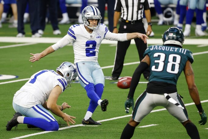 Dallas Cowboys' Hunter Niswander (1) holds as place kicker Greg Zuerlein (2) kicks a field goal under pressure from Philadelphia Eagles cornerback Michael Jacquet (38) in the first half of an NFL football game in Arlington, Texas, Sunday, Dec. 27. 2020. (AP Photo/Michael Ainsworth)