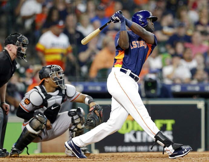 Houston Astros' Yordan Alvarez, right, watches his two-run home run in front of Baltimore Orioles catcher Pedro Severino, center, and umpire Lance Barksdale, left, during the fourth inning of a baseball game Sunday, June 9, 2019, in Houston. (AP Photo/Michael Wyke)