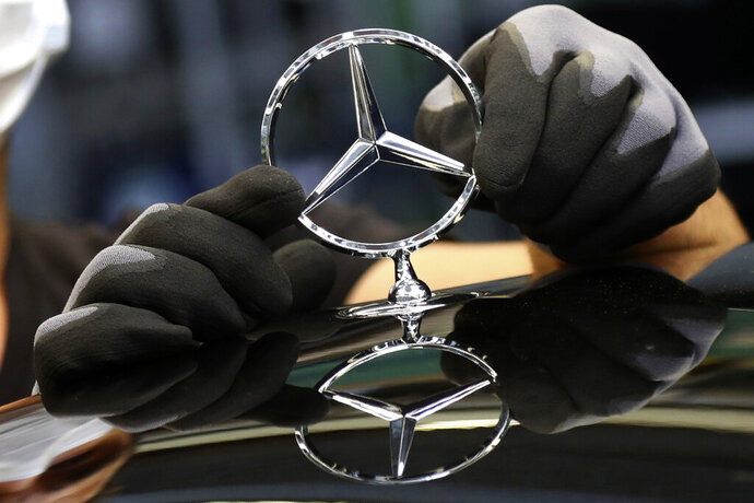 FILE - In this Thursday, April 30, 2020 file photo, an employee attaches a Mercedes emblem as he works on a Mercedes-Benz S-class car at the Mercedes plant in Sindelfingen, Germany. Daimler, maker of Mercedes-Benz vehicles, is reporting third-quarter earnings on Friday Oct. 22, 2020. (AP Photo/Matthias Schrader, file)