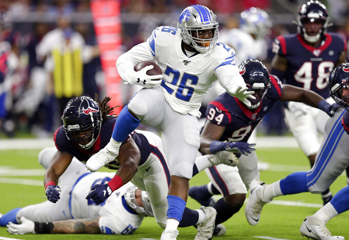 Detroit Lions running back C.J. Anderson (26) breaks away from Houston Texans linebacker Peter Kalambayi, left, during the first half of an NFL preseason football game Saturday, Aug. 17, 2019, in Houston. (AP Photo/Michael Wyke)