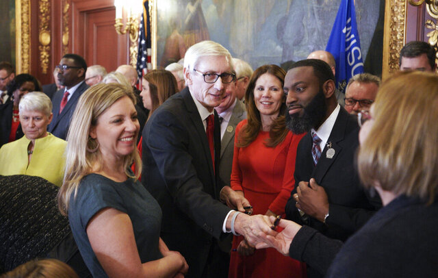 Wisconsin Govenor Tony Evers hands out pens after signing an executive order on Thursday Feb. 6, 2020. Wisconsin Governor Tony Evers held a press conference to sign an executive order for a special session which called for the Republican-controlled Legislature to spend $250 million of a state budget surplus on public schools.  (Steve Apps/Wisconsin State Journal via AP)