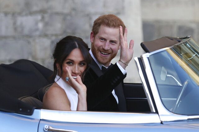FILE - In this Saturday, May 19, 2018 file photo the newly married Duke and Duchess of Sussex, Meghan Markle and Prince Harry, leave Windsor Castle in a convertible car after their wedding in Windsor, England, to attend an evening reception at Frogmore House, hosted by the Prince of Wales. Prince Harry and Meghan Markle are to no longer use their HRH titles and will repay £2.4 million of taxpayer's money spent on renovating their Berkshire home, Buckingham Palace announced Saturday, Jan. 18. 2020. (Steve Parsons/pool photo via AP, File)
